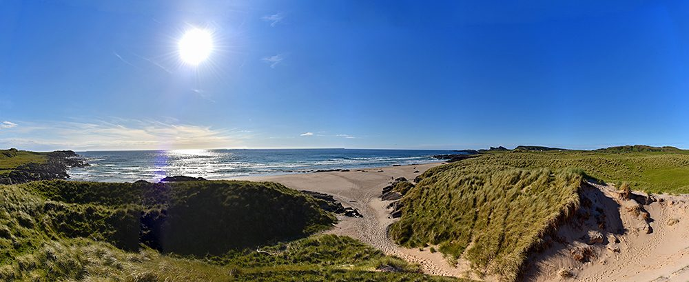 Panoramic picture of a coast with dunes and a beach, the June afternoon sun still high in the sky