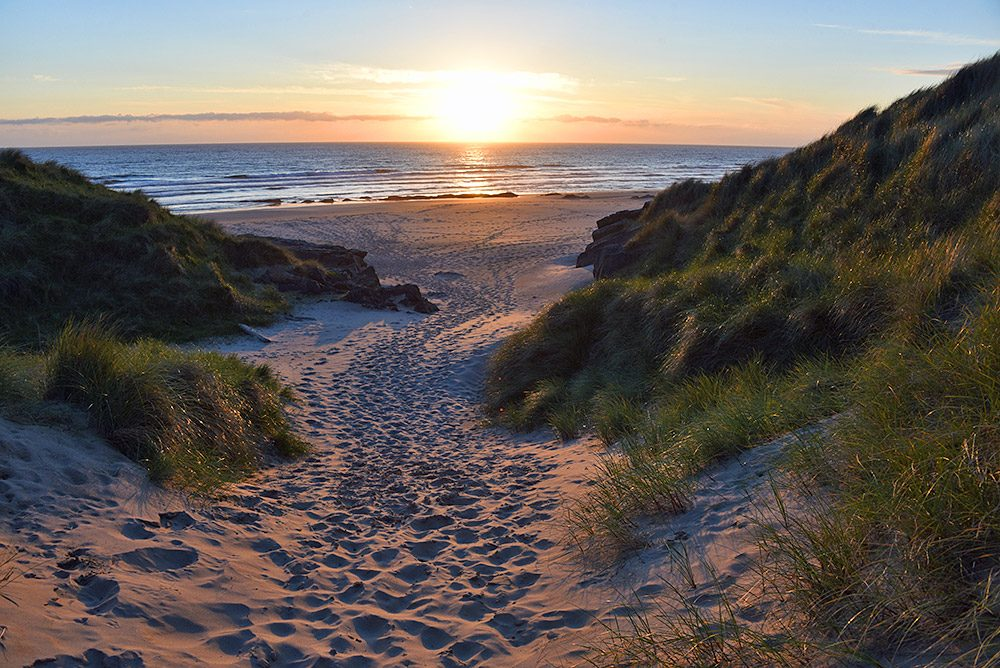 Picture of a sunset over a bay with a beach, seen through some high dunes