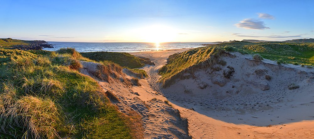Panoramic picture of a sunset seen through a gap between dunes behind a beach