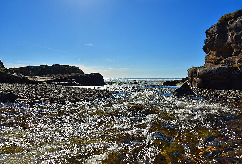 Picture of a small river flowing rapidly towards a beach and a bay on a sunny summer day