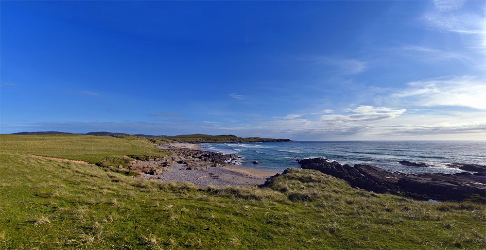 Panoramic picture of a view over a bay with a beach, rocks and dunes