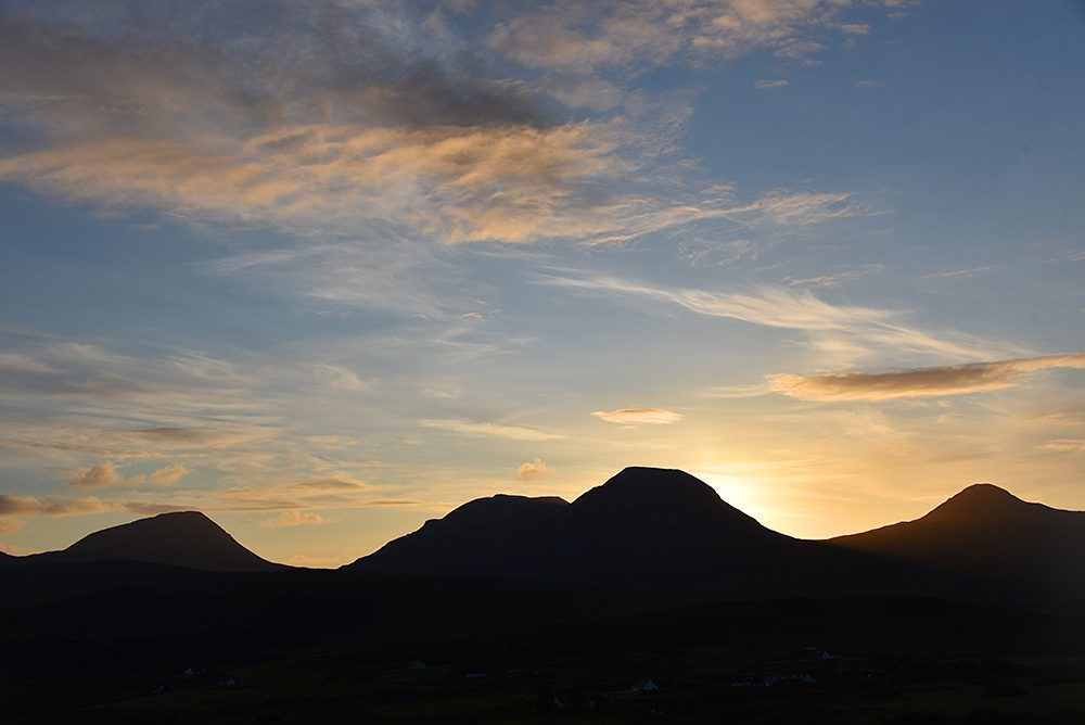 Picture of a sunset behind the silhouette of several mountains