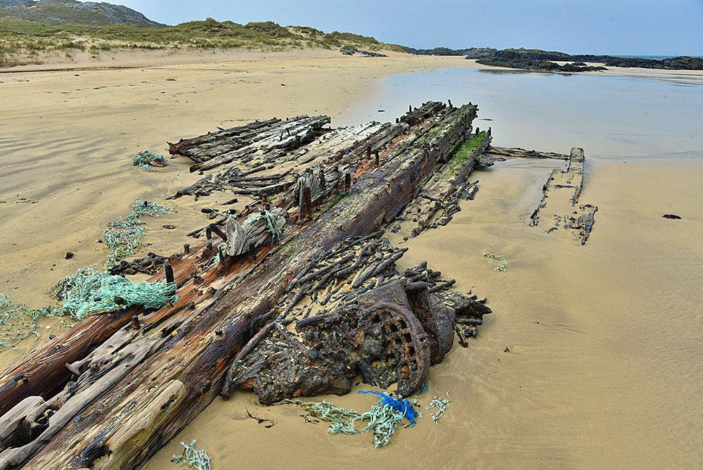 Picture of the wreck of an old steam ship on a beach, only a few planks and bolts remain