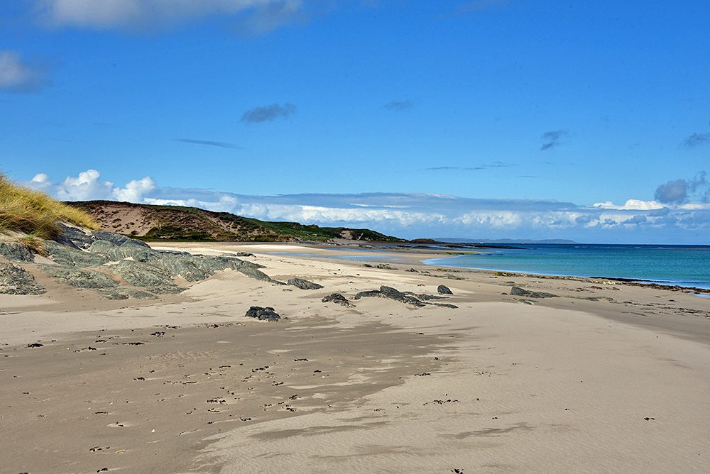 Picture of a coastal landscape with a beach and dunes on an island, another island on the horizon