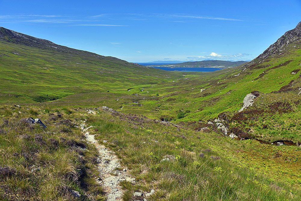 Picture of a path leading into a glen (valley) with a loch in the distance