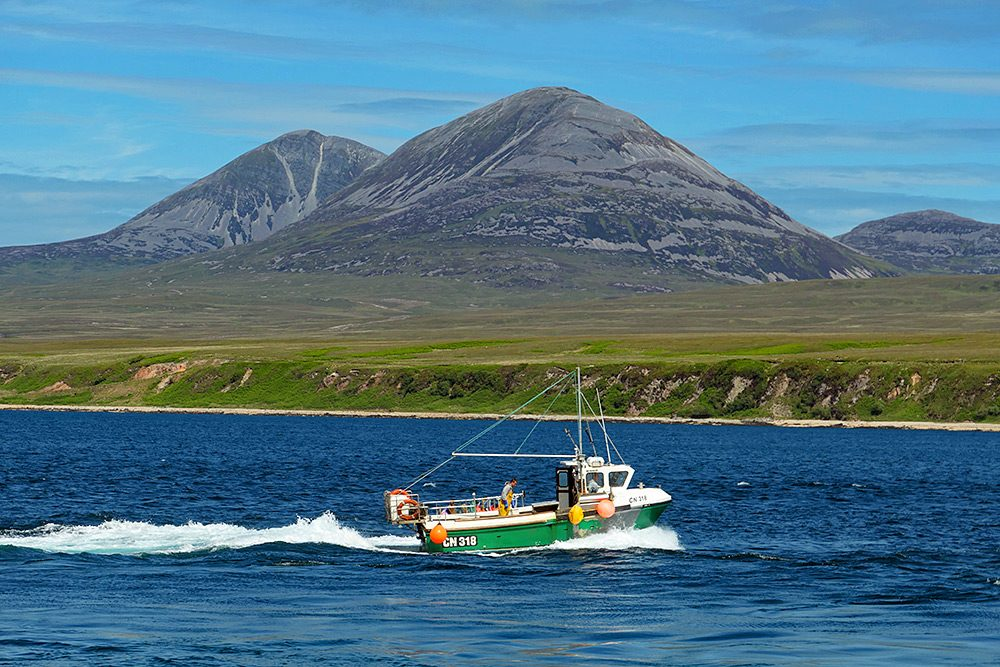 Picture of a fishing boat with the registration CN318 in a sound between two islands, two large mountains on the other side