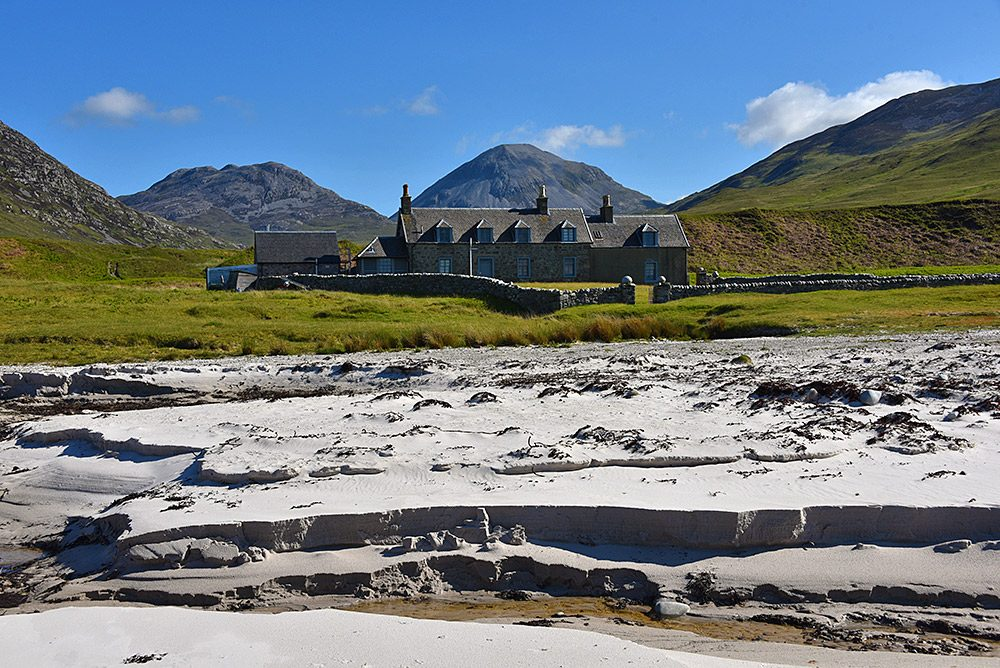 Picture of a lodge in a remote location seen from a beach, mountains in the background