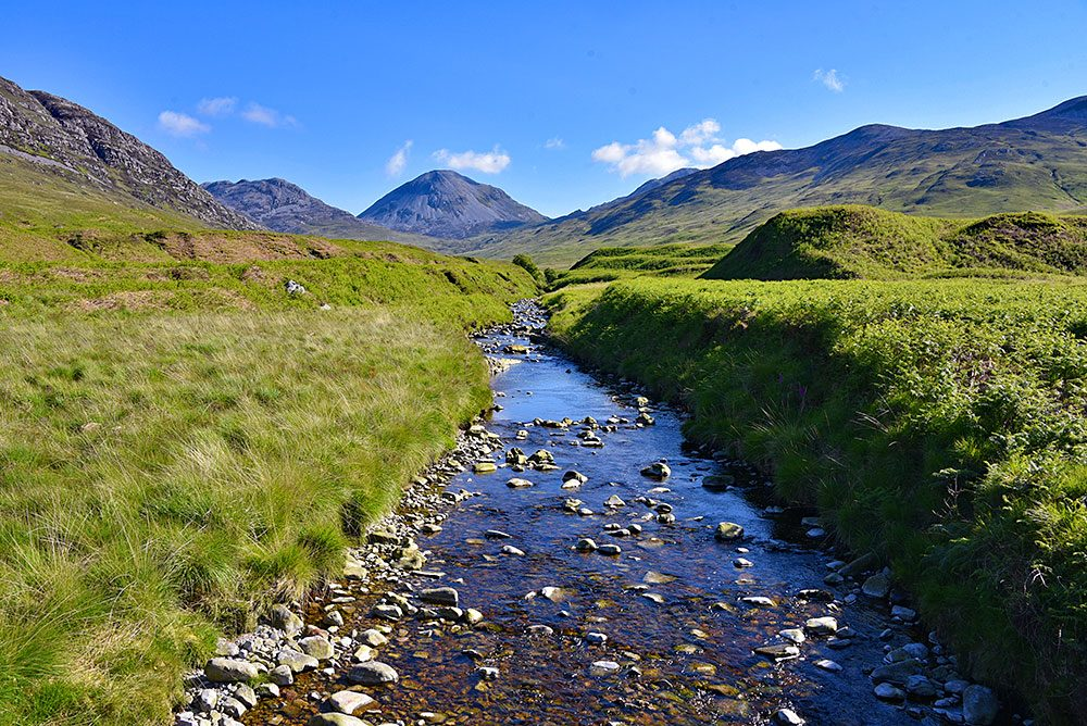Picture of a small river flowing down a glen (valley), a scree covered mountain in the distance