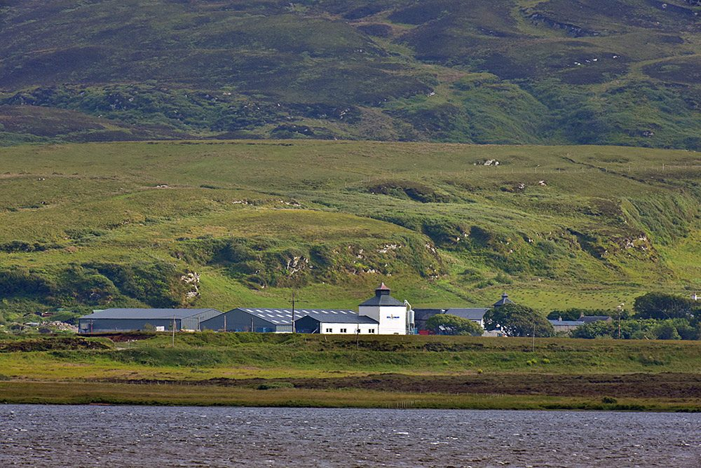Picture of a farm distillery seen across a loch (lake)