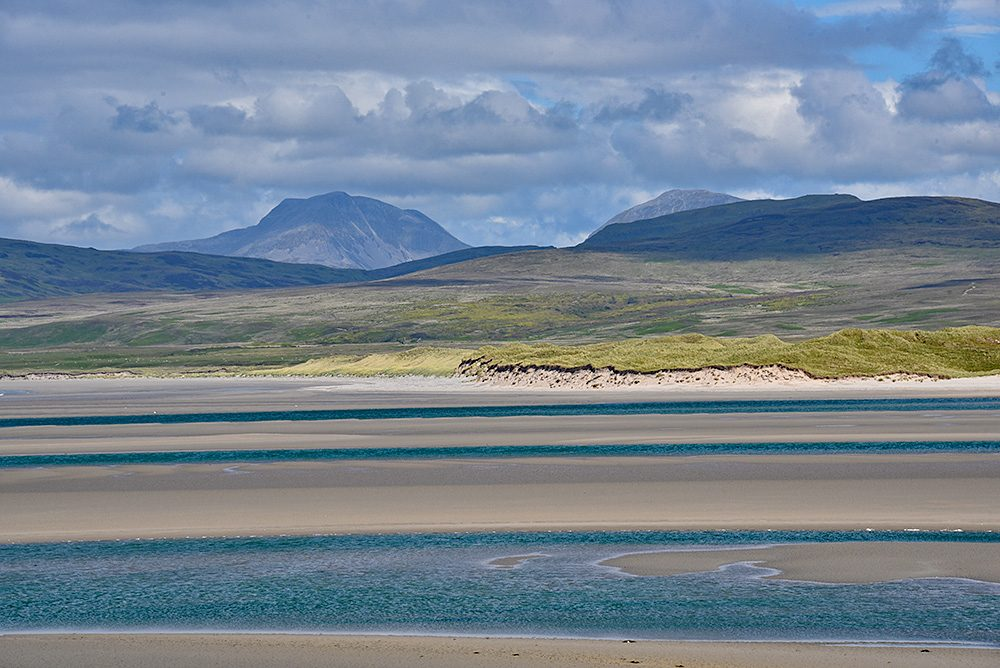 Picture of a view across a sea loch at low tide, dunes on the other side with some mountains in the background