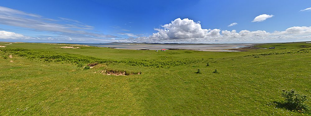 Panoramic picture of a view over a sea loch at low tide from a row of dunes