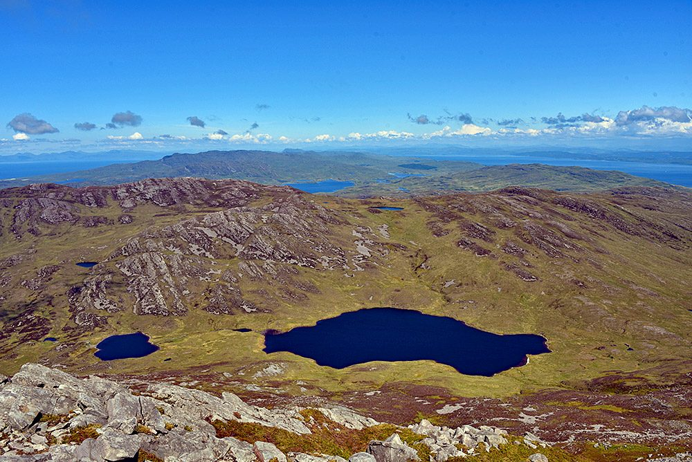 Picture of a view from a mountain over an island, two freshwater lochs below, a sea loch in the distance