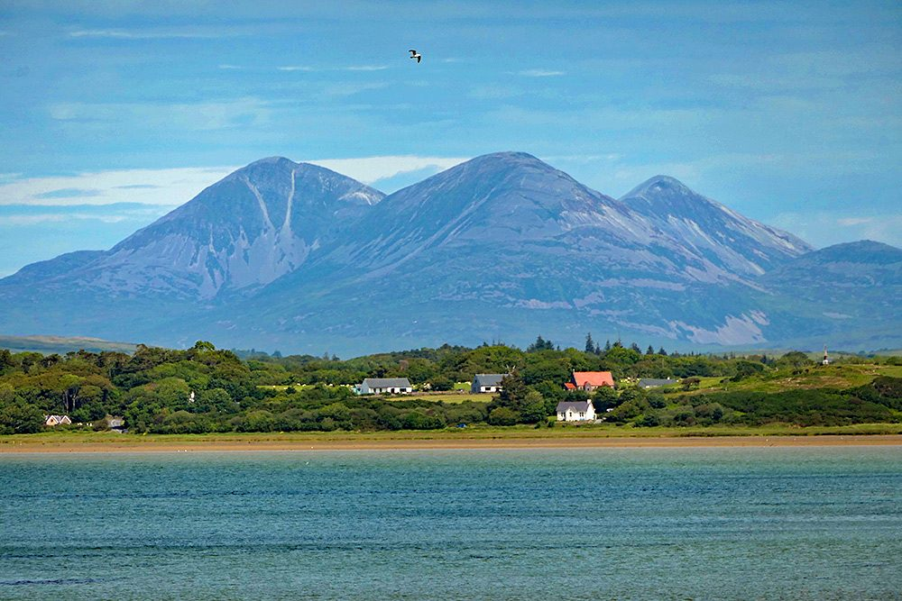 Picture of three mountains towering over some houses on lower land, seen across a sea loch