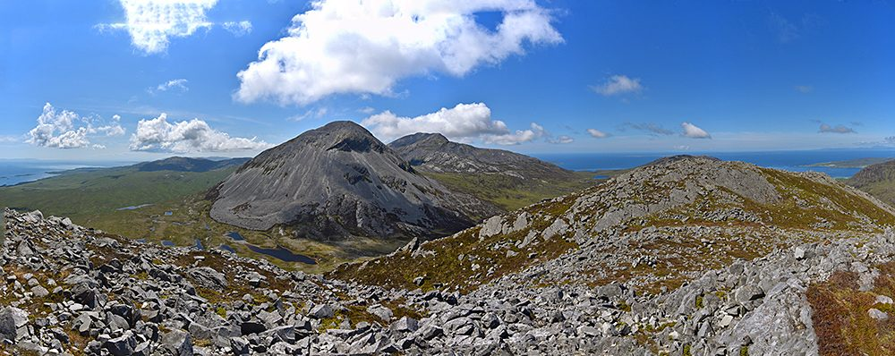 Panoramic picture of a view from the top of a mountain, looking over two other scree covered mountains