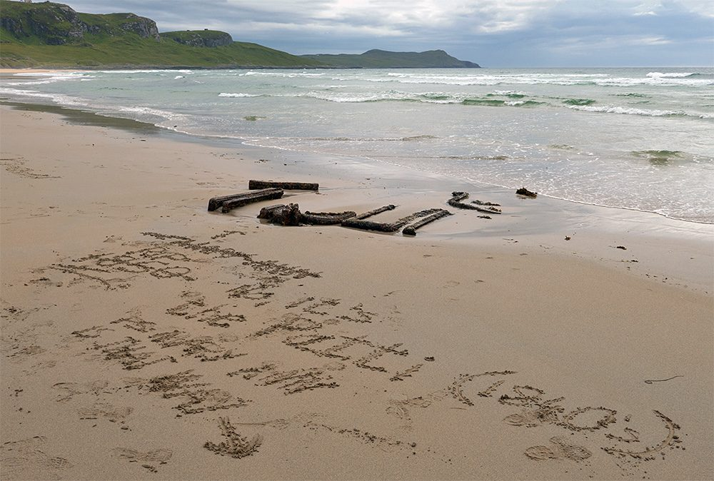 Picture of writing in the sand on a beach, correcting a mistake in an earlier writing