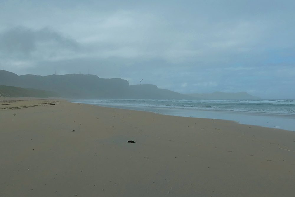 Picture of beach with crags at the end during a rain shower