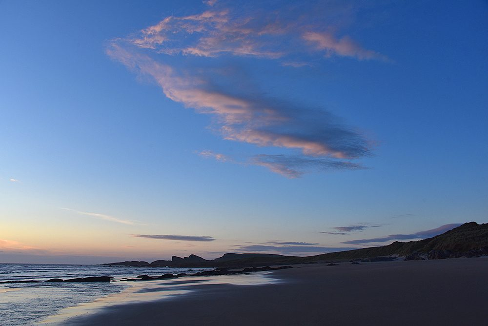Picture of a beach with dunes and rock formations in the evening light just before sunset