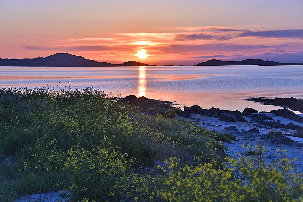 Picture of a sunrise at a bay with a few small islands dotted around