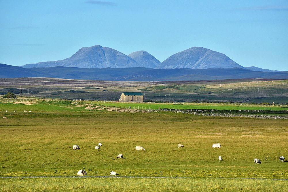 Picture of three mountains seen across a big wide landscape
