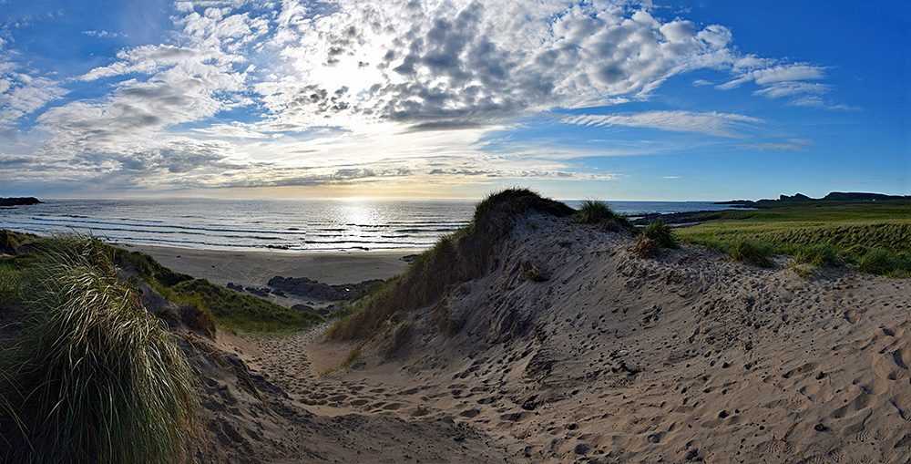 Panoramic picture of a view from a dune above a beach and coastal landscape