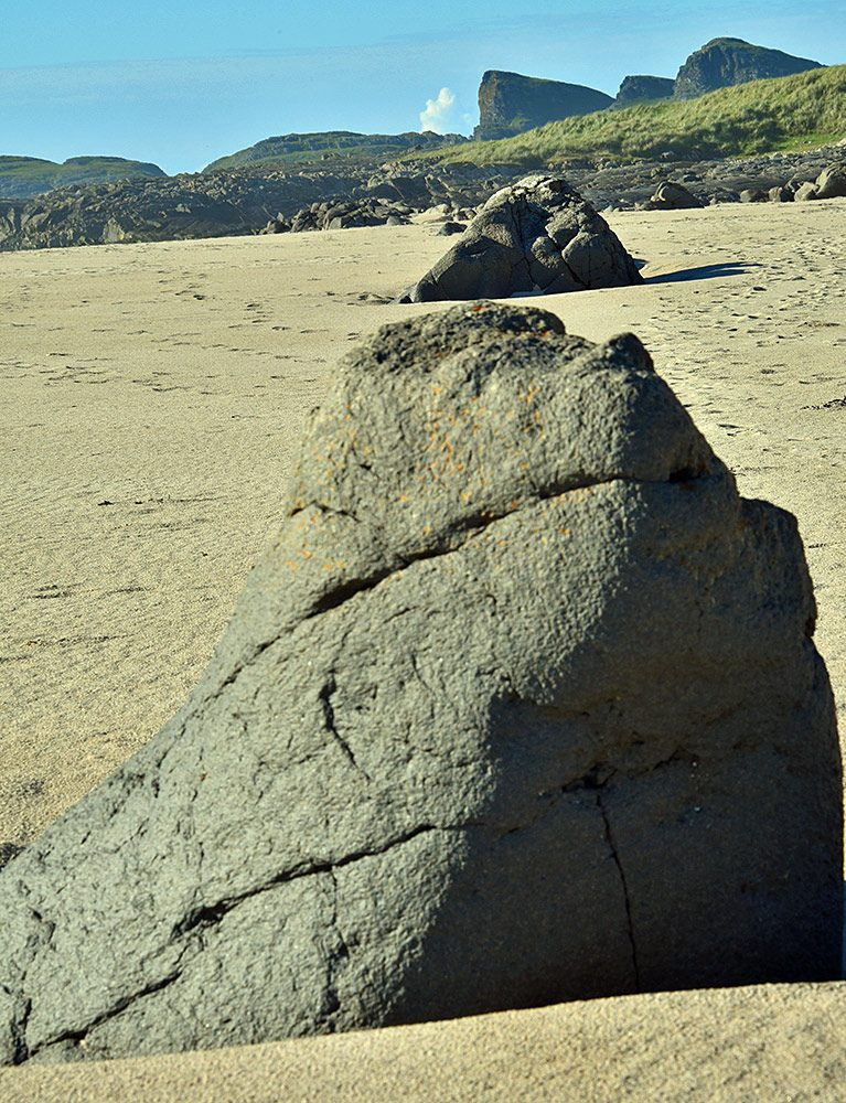 Picture of two large stones on a beach with a rock formation in the background