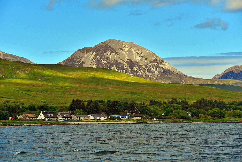 Picture of a scree covered mountain towering over a coastal village