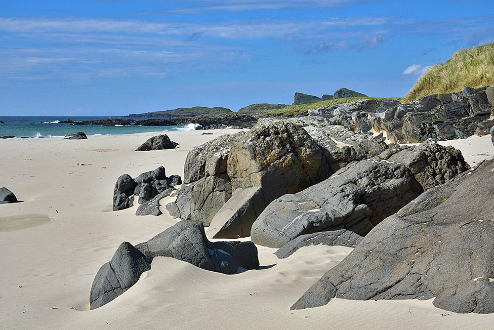 Picture of large rocks on a beach below some dunes