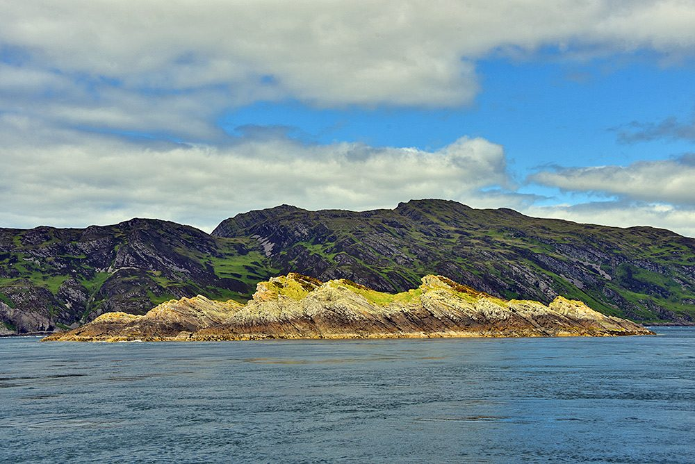 Picture of a very small rocky island (more an outcrop) off a much larger island