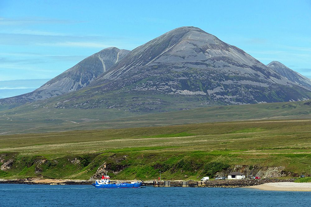 Picture of a small ferry berthing at a slipway, three large mountains in the background