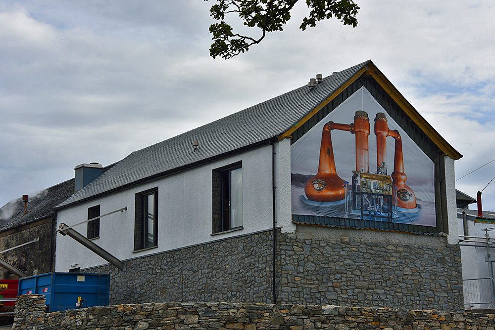 Picture of a farm distillery with one side covered by a poster with stills
