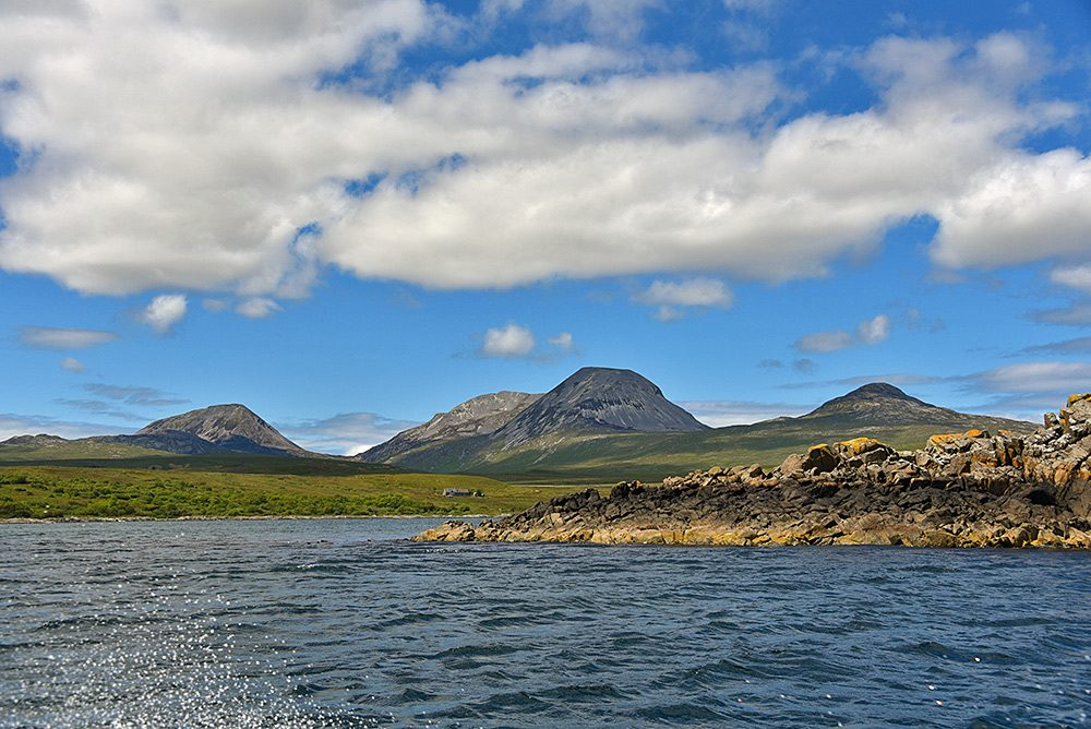 Picture of a view across a bay towards four mountains, seen from the water