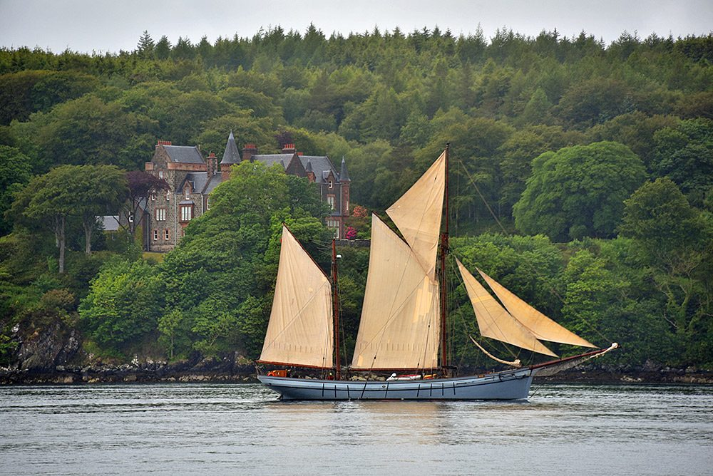 Picture of an old ketch under sail passing an old stately home on a hillside above a sound between two islands