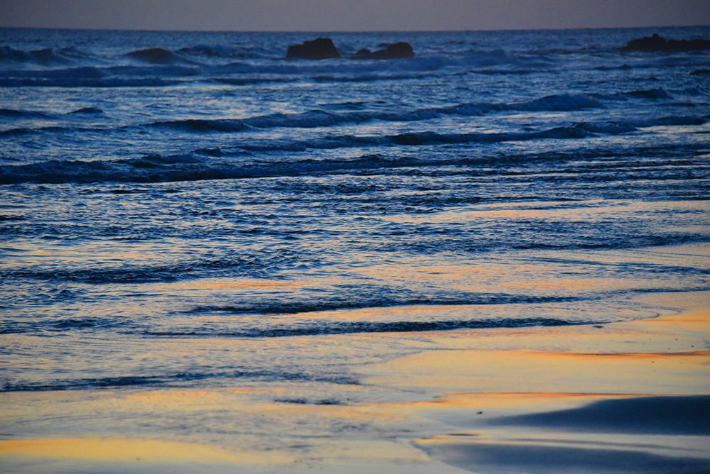 Picture of some small waves rolling on to a beach in the last light of the gloaming
