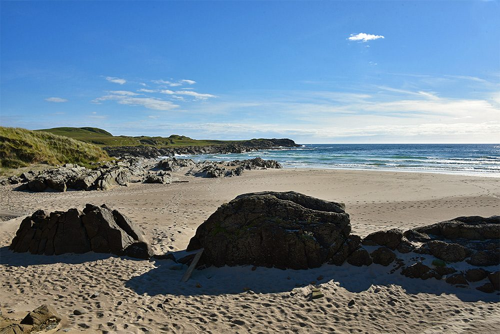 Picture of a sandy beach with most of it behind some large rocks in the sand