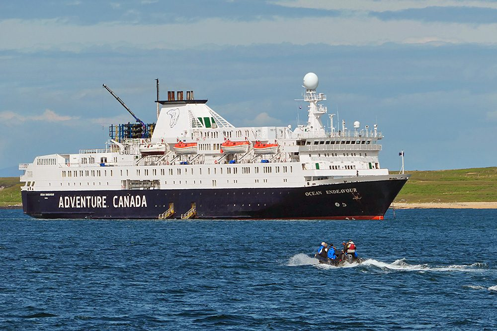 Picture of a small tender on its way to a moored cruise ship in a sound between two islands