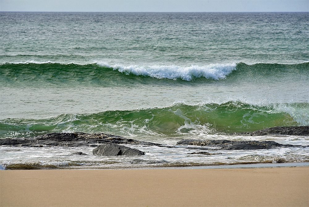 Picture of two waves breaking as they approach a beach with a few rocks