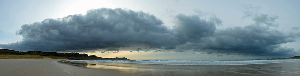 Panoramic picture of a bank of clouds over a wide bay with a beach