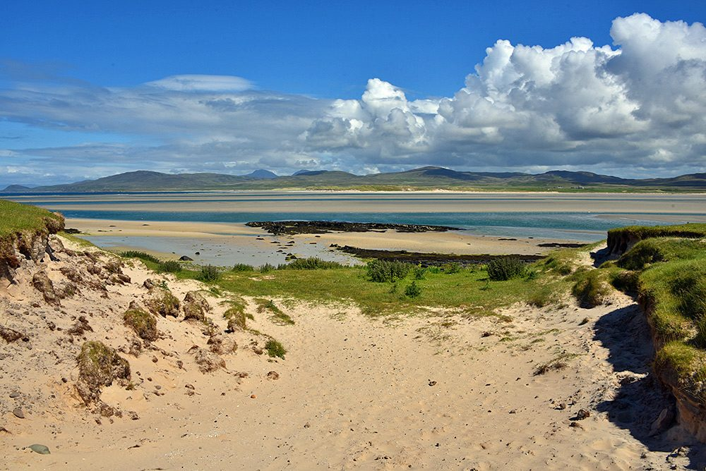 Picture of a sea loch at low tide, seen through a gap between dunes