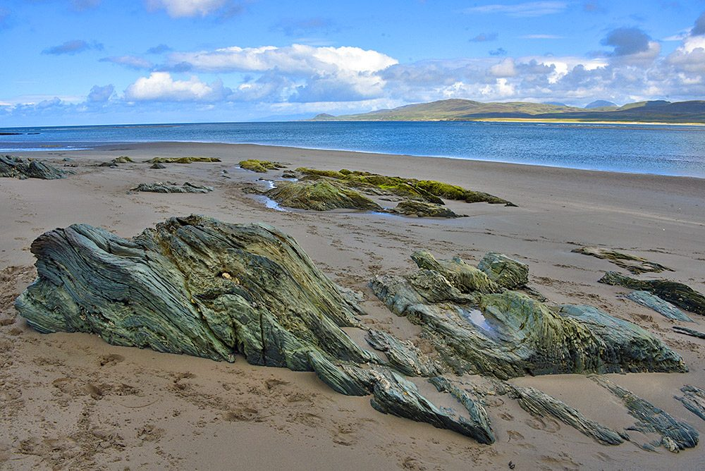 Picture of interestingly shaped rocks on a beach next to a sea loch