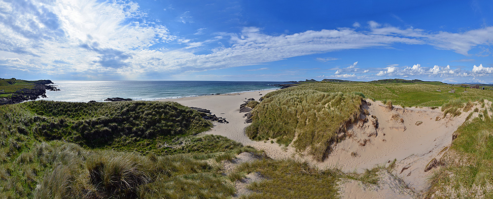 Panoramic picture of a from a dune over dunes, a beach and a bay