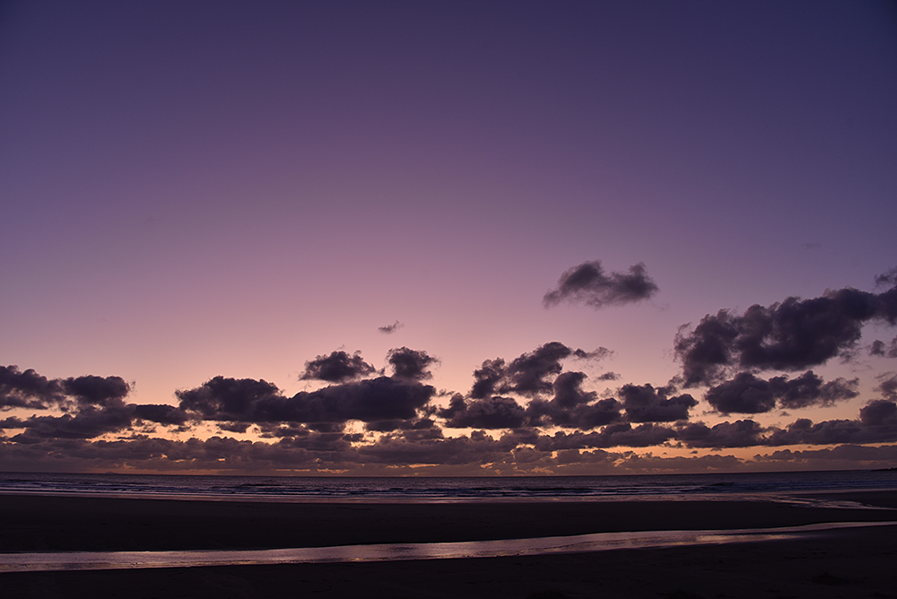Picture of some distant clouds over a bay with a beach in the last light of the gloaming