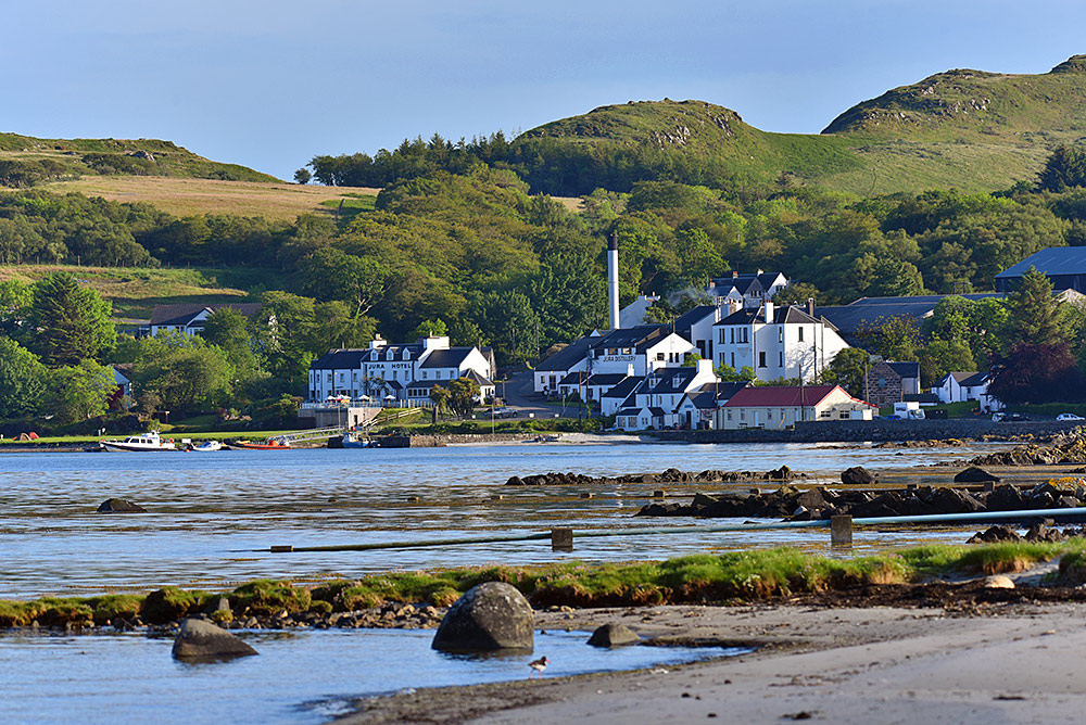 Picture of a coastal village with a hotel and a distillery in the mild June evening sun
