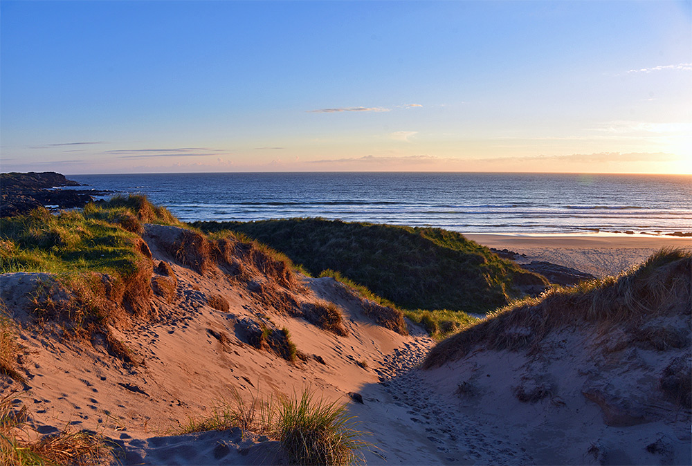 Picture of a view down a gap in some dunes, one side in the sunset sunshine, the other in the shadow