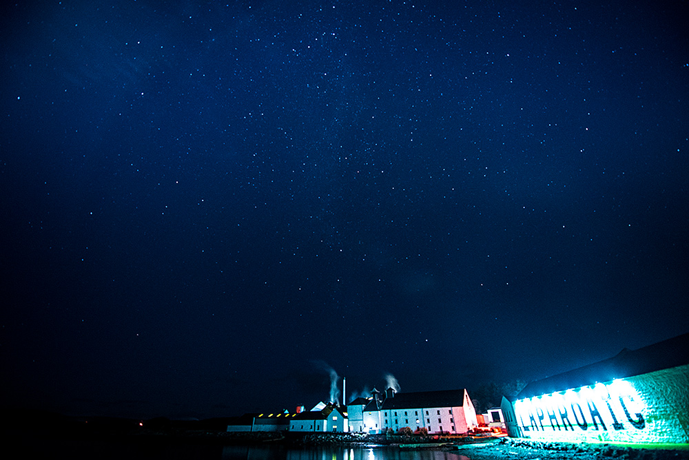 Picture of a coastal distillery (Laphroaig on Islay) under a starry night sky