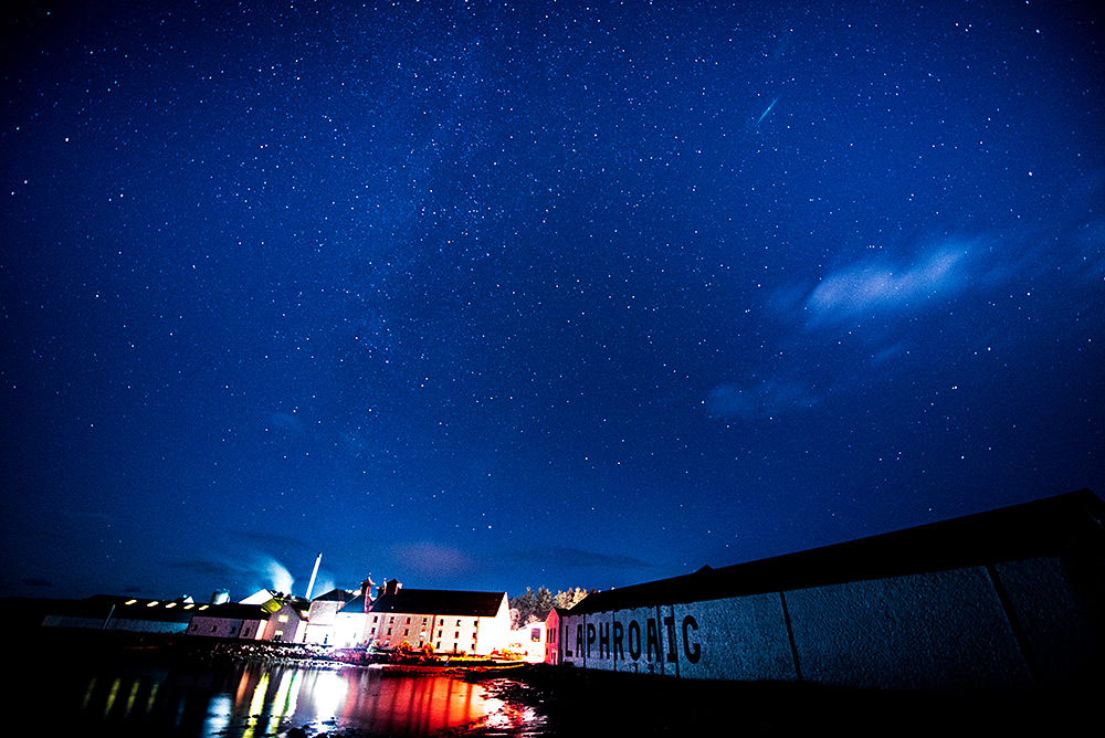Picture of a starry night sky over a coastal distillery (Laphroaig on Islay)
