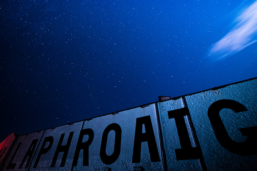 Picture of a starry night sky over the Laphroaig distillery lettering on the warehouse
