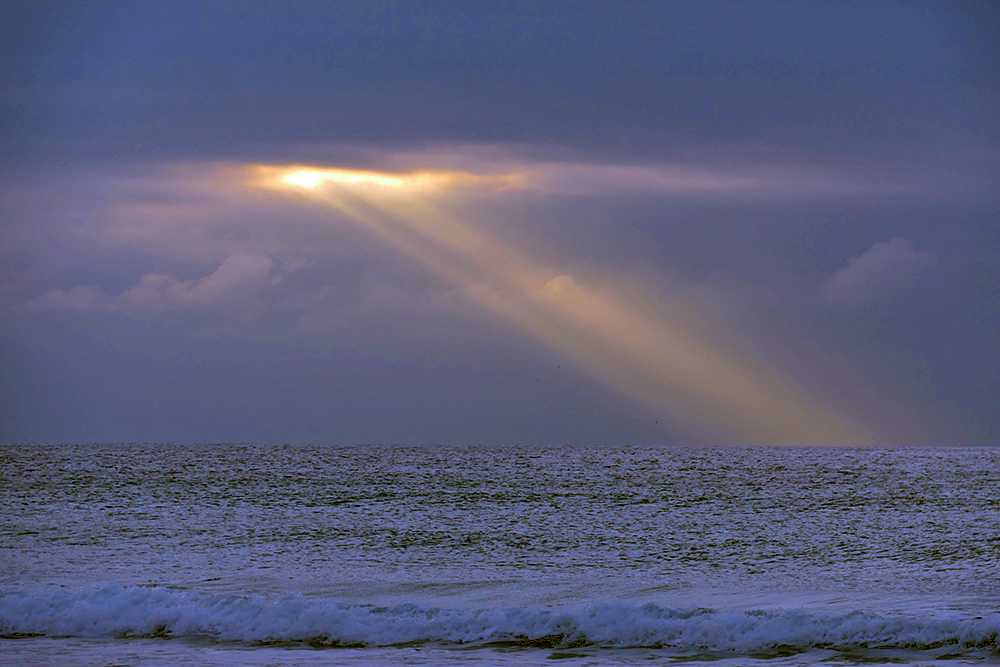 Picture of a ray of sunlight breaking through clouds over the ocean