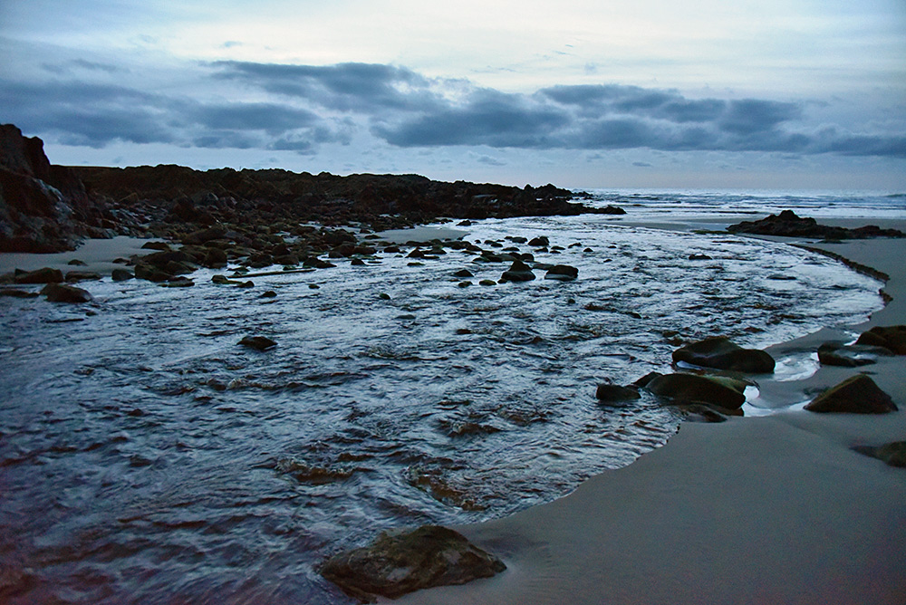 Picture of a small river running across a beach into the sea in the evening gloaming