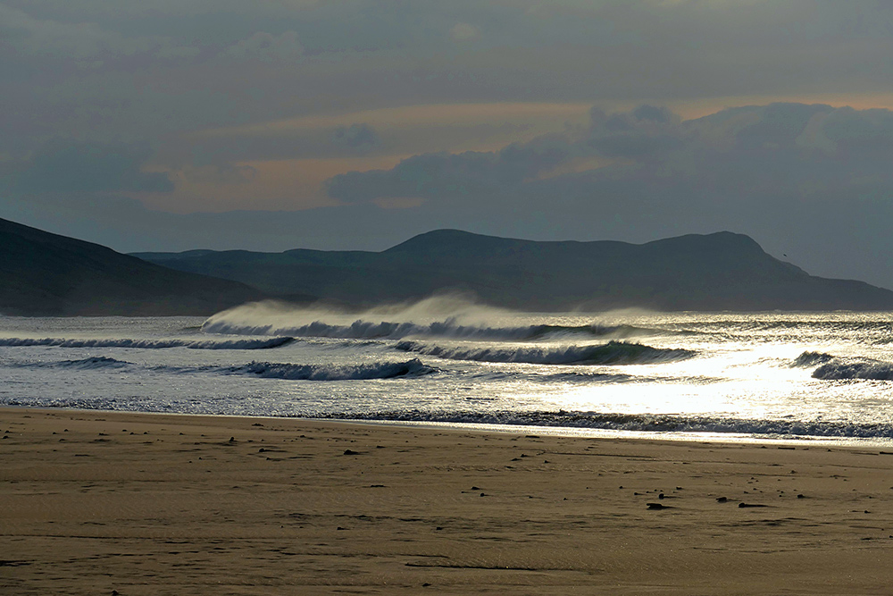 Picture of waves breaking and the spray blowing backwards in the golden winter afternoon sun
