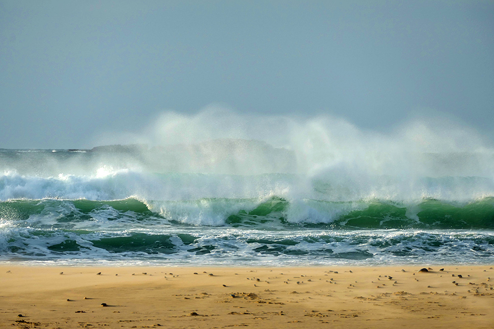 Picture of waves breaking and the spray blowing backwards just off a golden sandy beach
